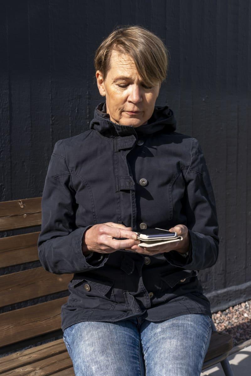 Anu Raijas, Suomen Pankin talousosaamisen neuvonantaja tutkailee puhelinta pihapenkillä