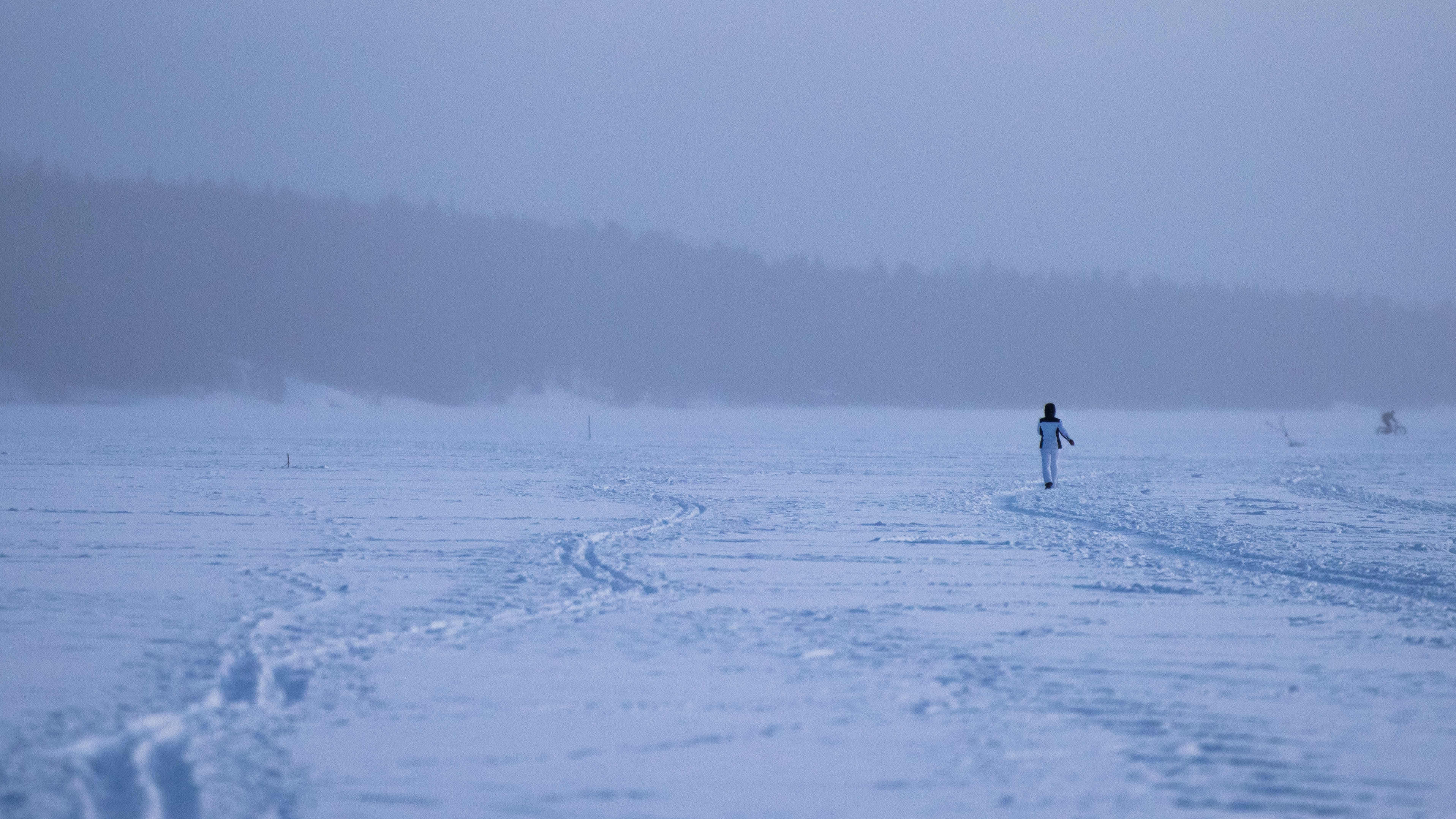 Henkilö kävelee kaukana meren jääkkä lumisateessa.