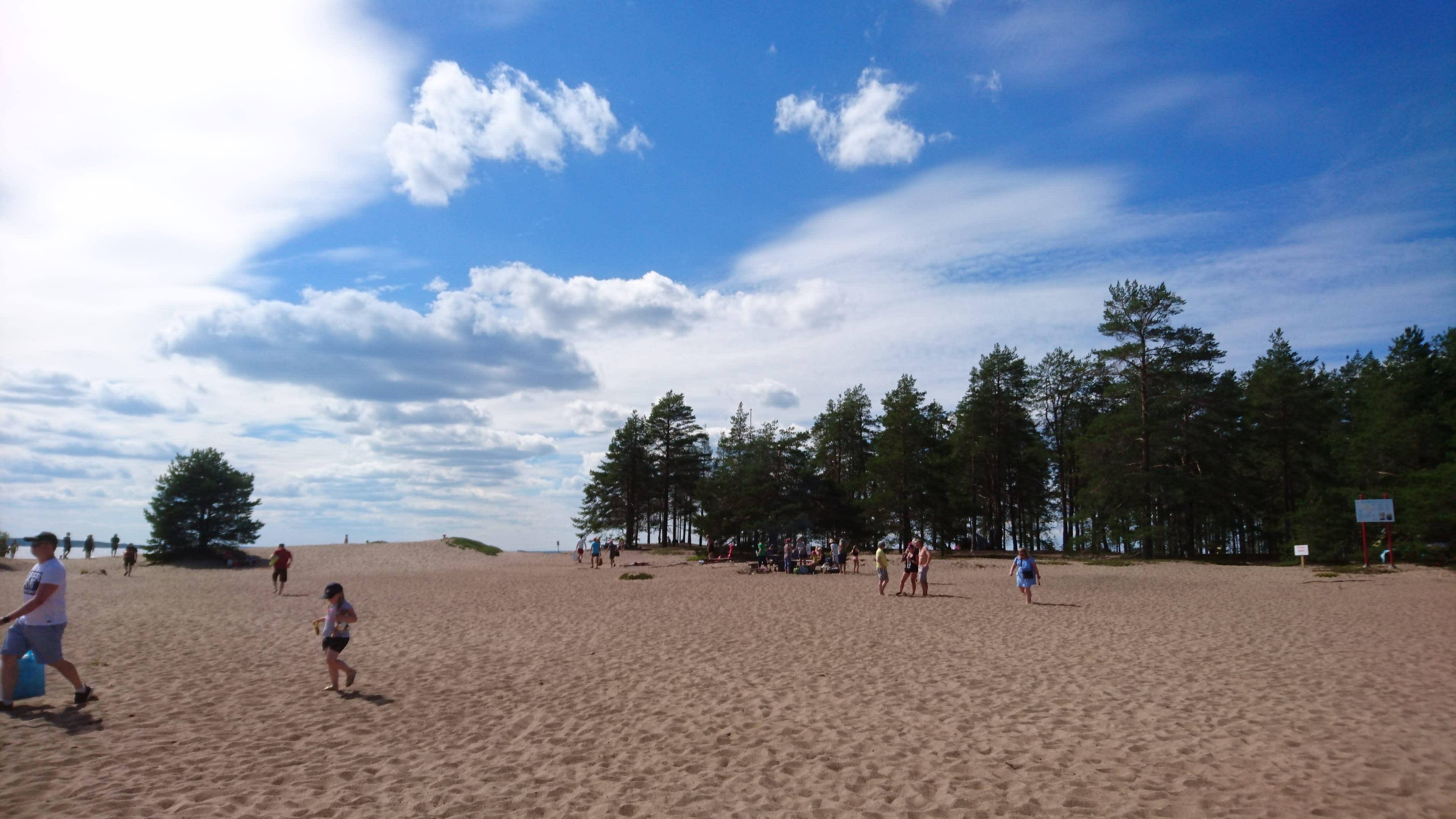 Ihmisiä Ärjänsaaren hiekkarannalla.