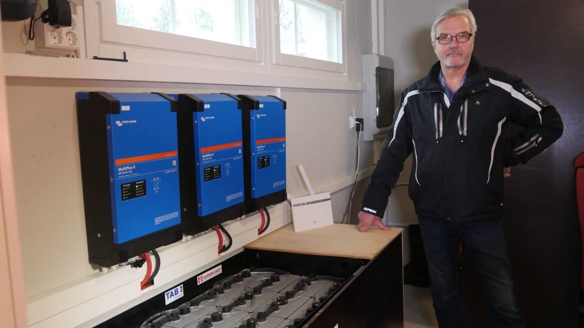 Jukka Heinonen laitehuoneessa, jossa akusto ja kolmivaiheinvertterit seinällä.