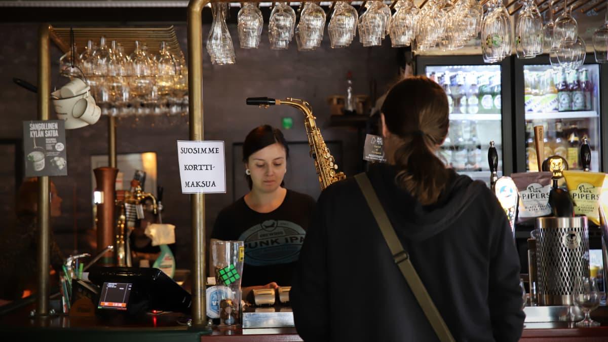 Baarimikko Henna Vartiainen palvelee asiakasta joensuulaisessa 60's Palaver -olutravintolassa.
