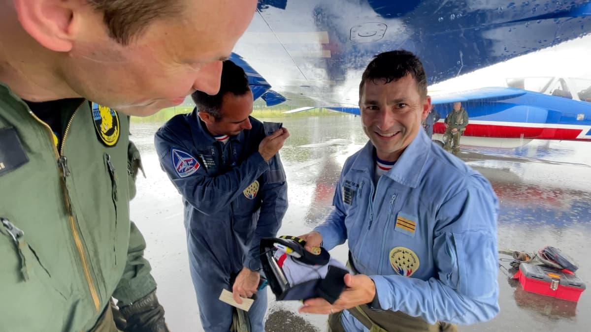 Grégory Leopold Metzger (oik.) lentää ryhmän johtajan takana vasemmalla. Hän kyyditti Marc Fussia (vas.) harjoituslennolla. Mukana kuvassa on myös Metzgerin mekaanikko Philippe Colin. Kolmikko siirtyi lennon jälkeen sateensuojaan koneensa siiven alle.