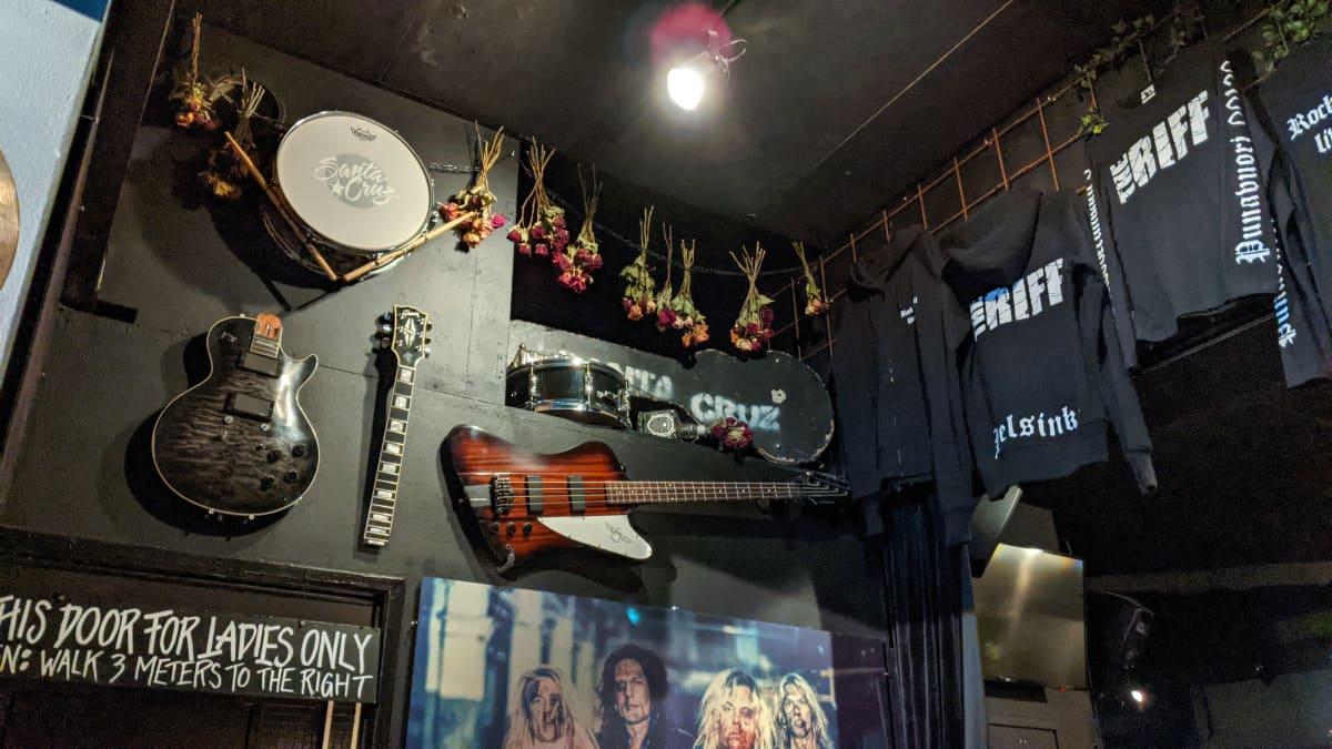 Erilaisia soittimia ja mainospaitoja The Riff -baarin seinällä.