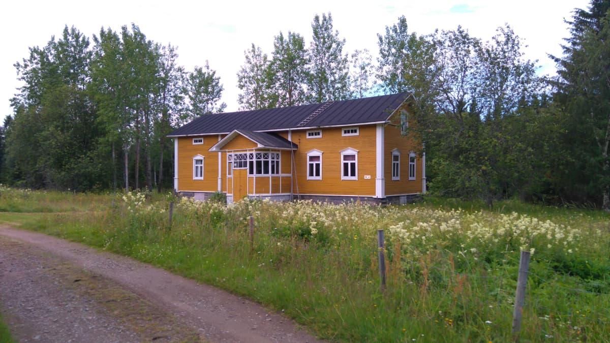 Pahnilan keltainen museorakennus, etualalla kesäinen niitty