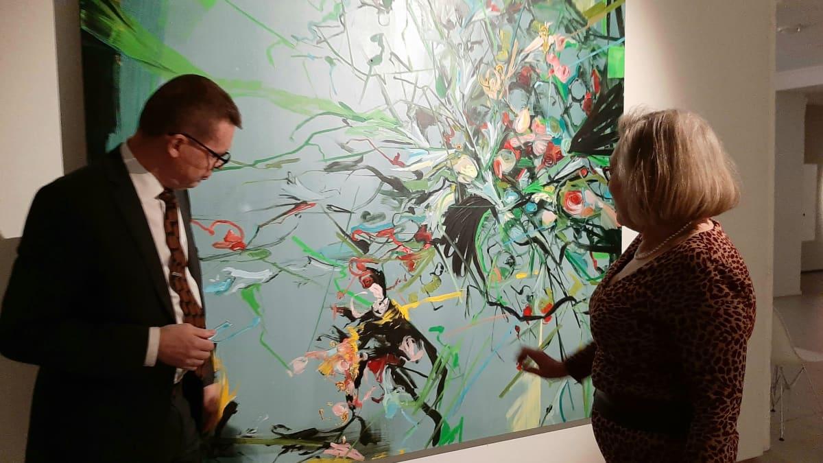 Kuntsin säätiön puheenjohtaja Markku Lumio ja asiamies Anne-Maj Salin tarkastelevat Jukka Rusasen maalausta.
