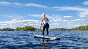 Tiia Vepsäläinen sup-lautailee Saimaalla Lappeenrannan Myllysaaren rannassa.