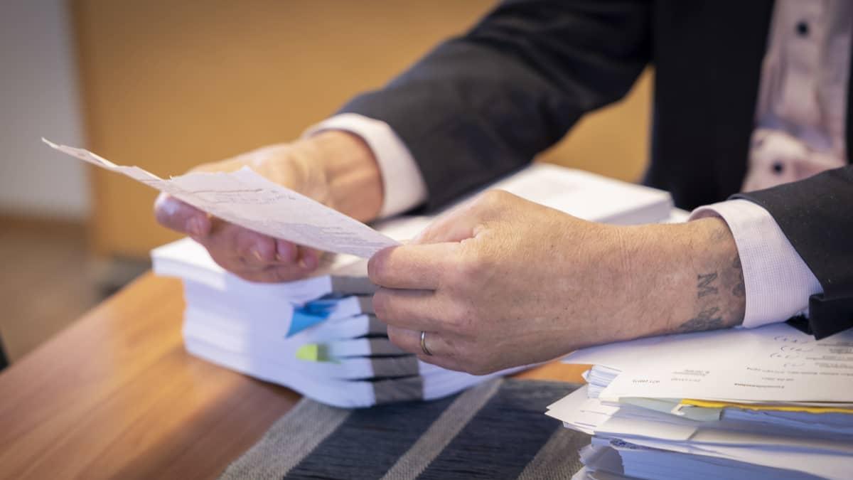 Mies pitelee paperia käsissään.