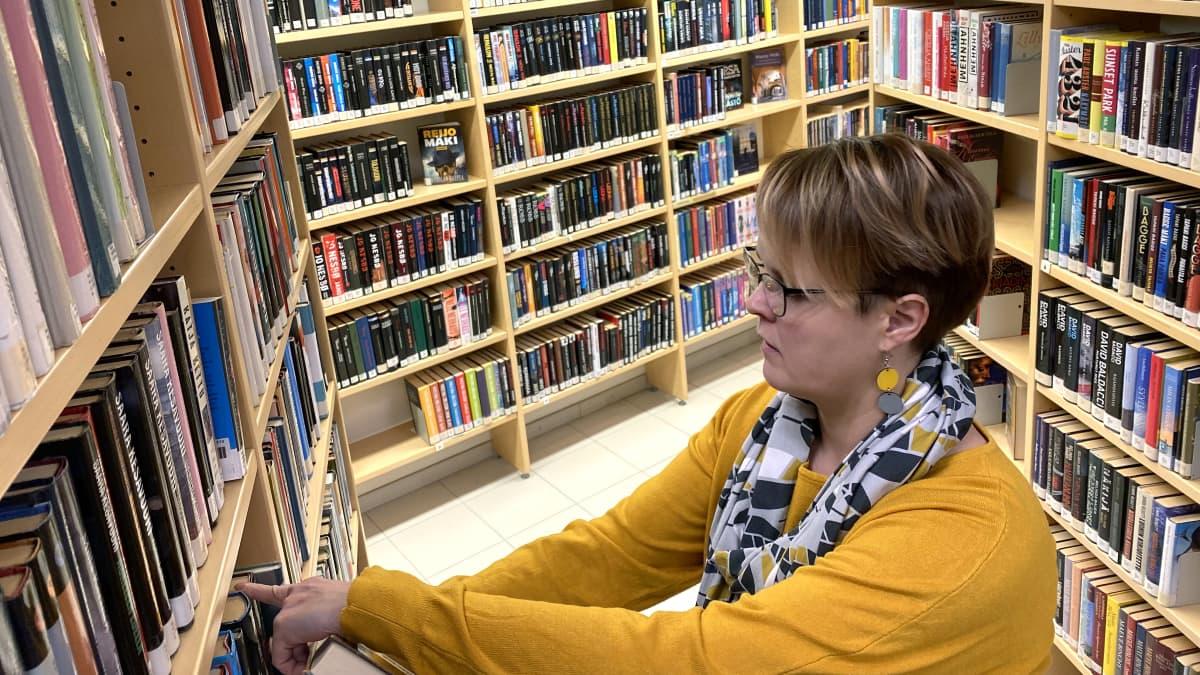 Kuvassa kirjastotyöntekijä hyllyttää kirjoja