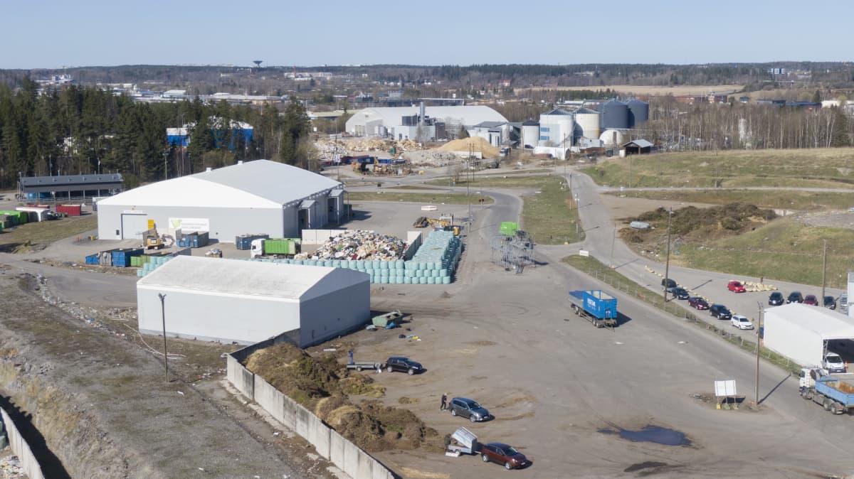 Ilmakuva Topinojan jätekeskuksesta: puutarhajätekasa, taustalla rakennuksia.