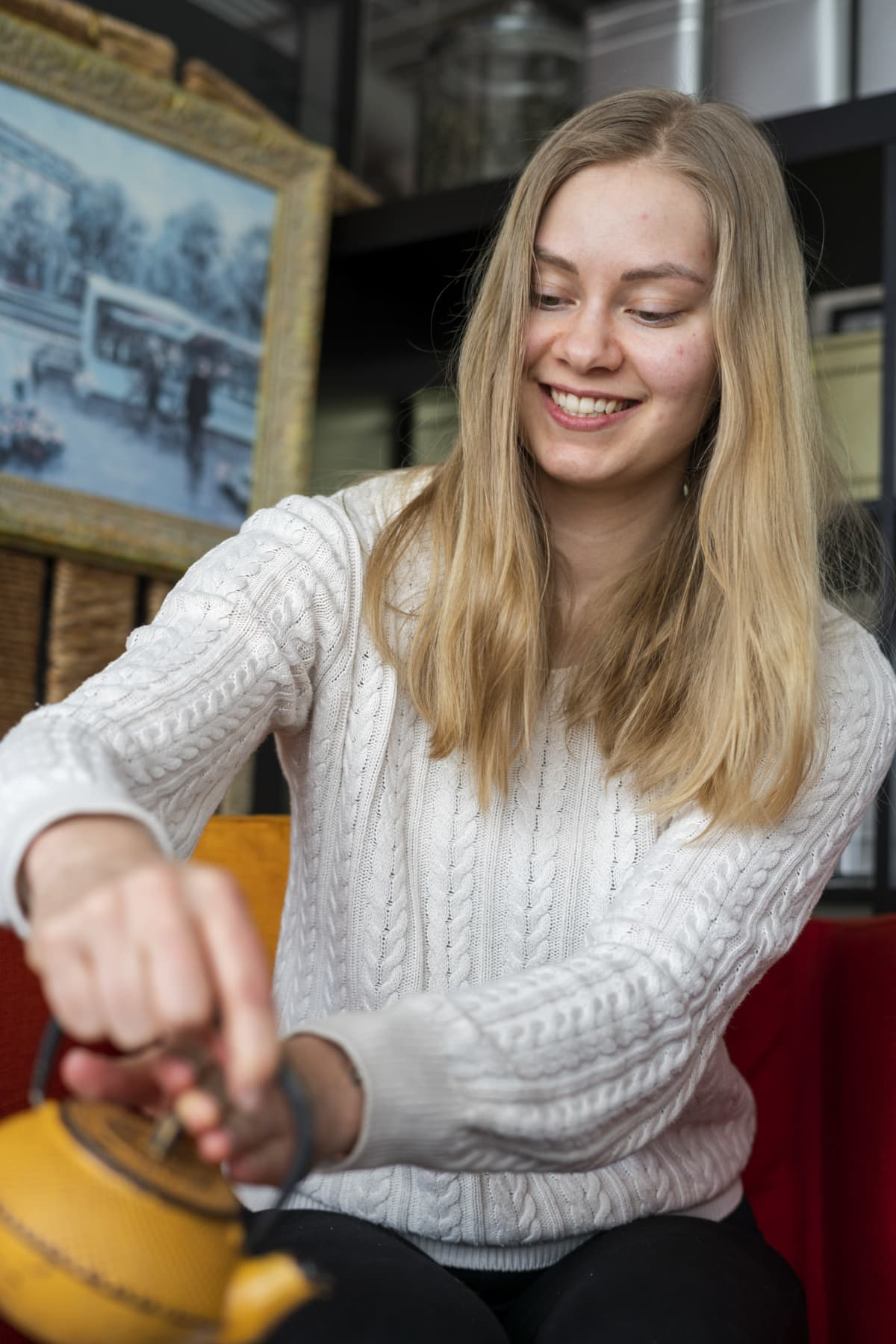 Vaaleahiuksinen nainen kaataa teetä kuppiin pannusta.