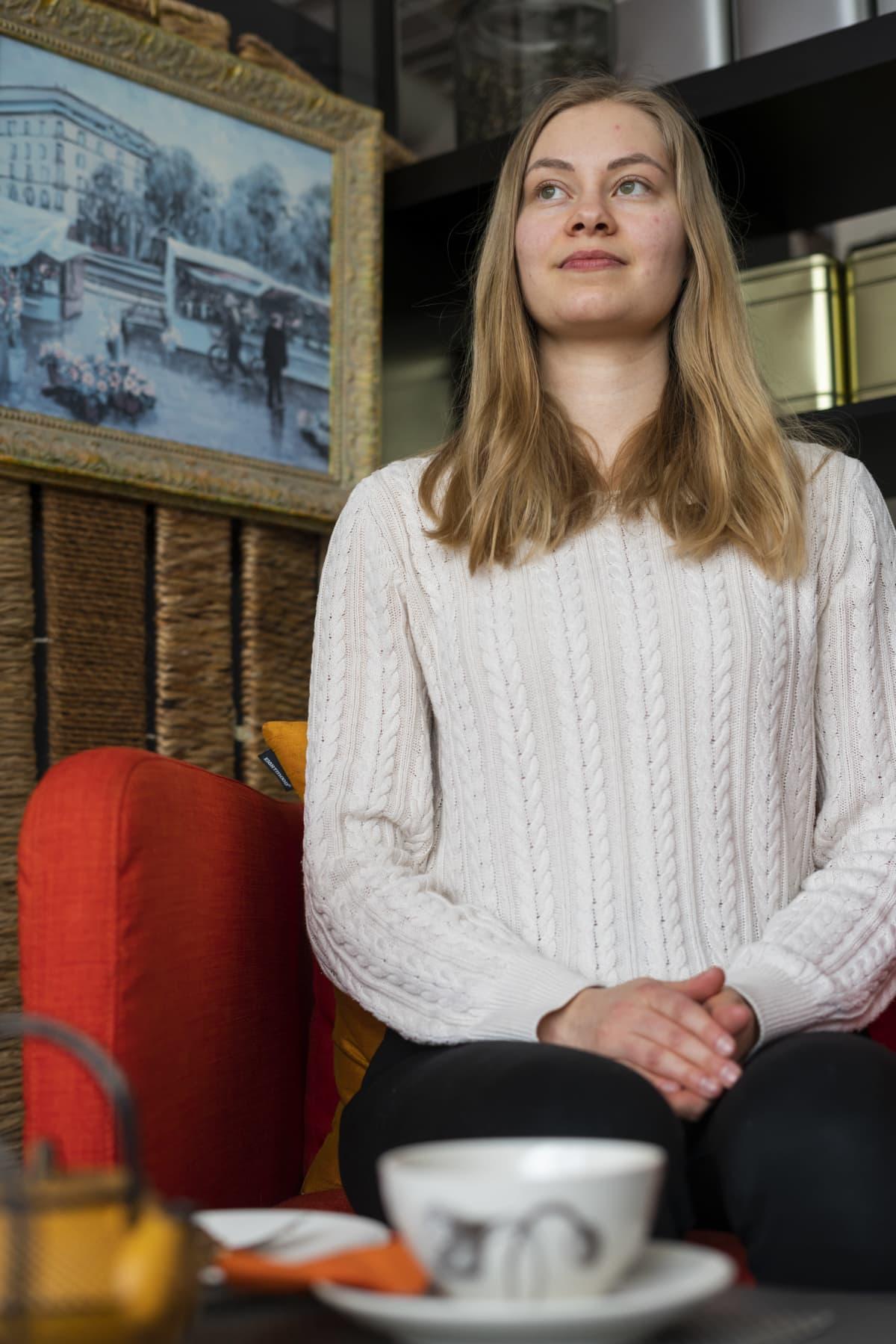 Vaaleahiuksinen nainen istuu punaisella sohvatuolilla.