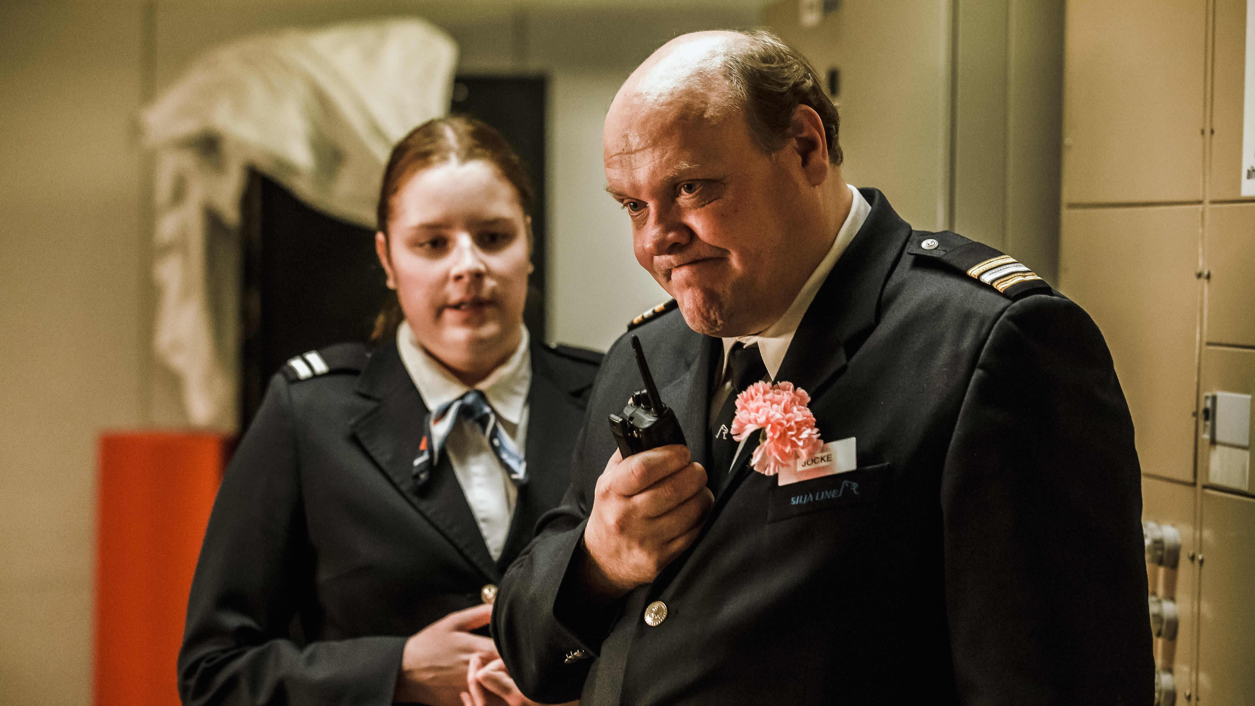 Hannu-Pekka Björkman seisoo nyrpeännäköisenä radiopuhelin kädessään.