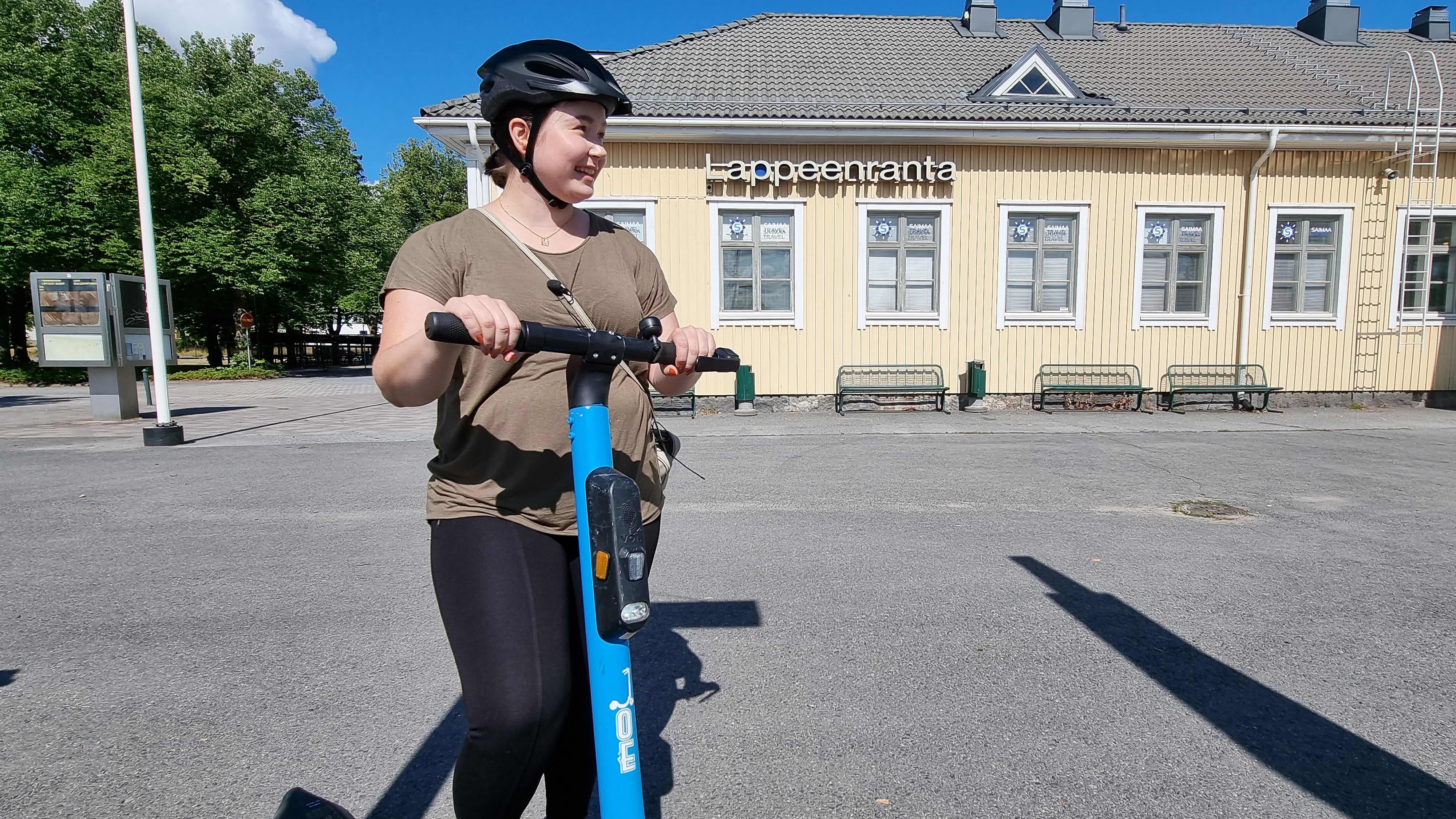 toimittaja Marika Anttonen sähköpotkulaudalla Lappeenrannan rautatirasemalla