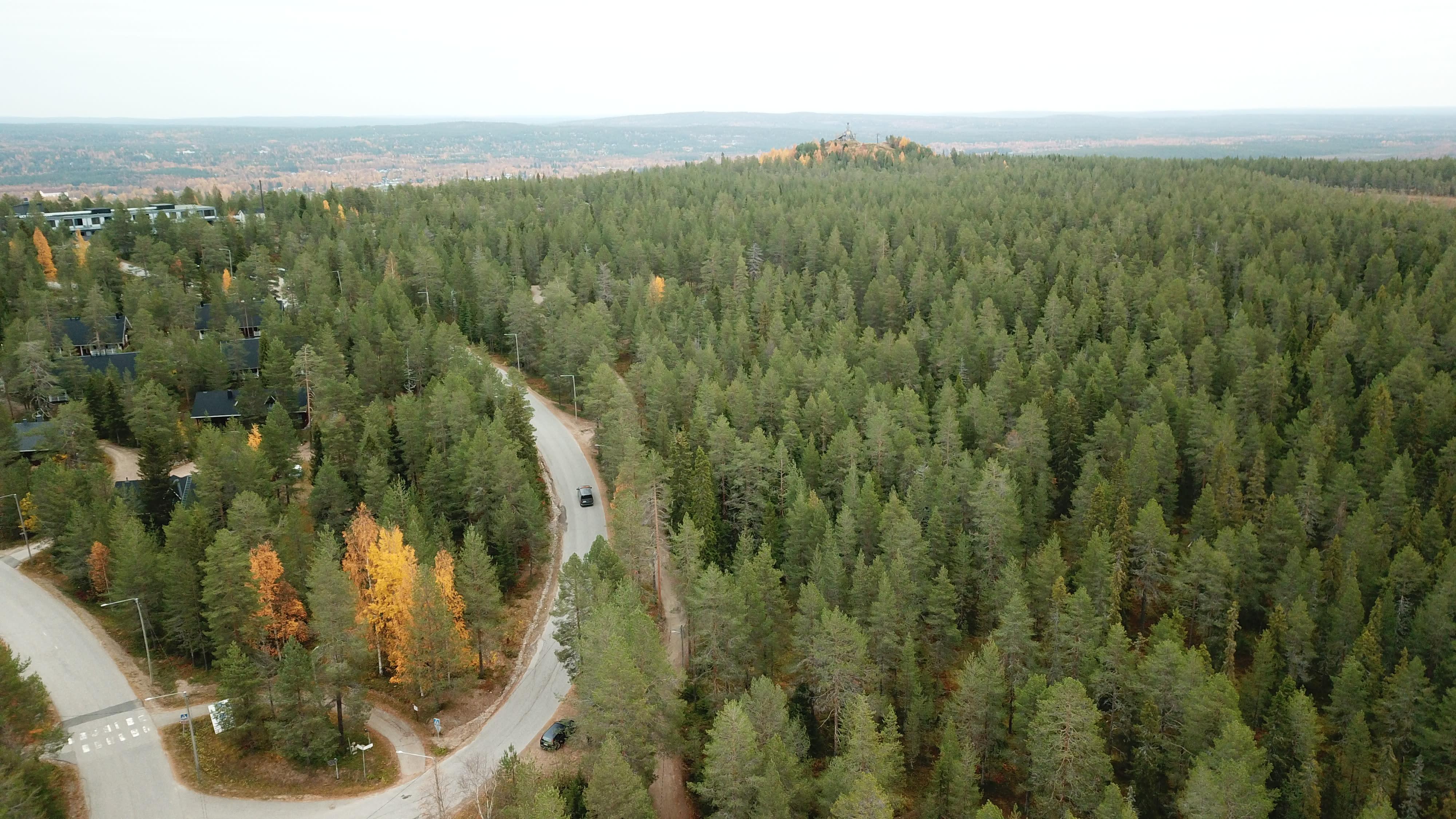 Ilmakuva Ounasvaaralta, alla näkyy metsää ja tie, jolla ajaa auto.