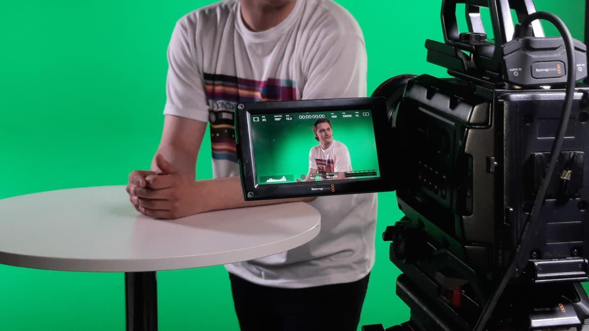 Vihreän lakana edessa olevaan studion pöytään nojaava Jokim Viljamaa näkyy kameran esikatseluruudusta