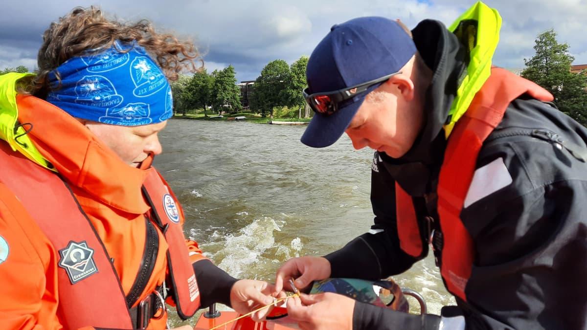 Kaksi henkilöä tutkii veden laatua