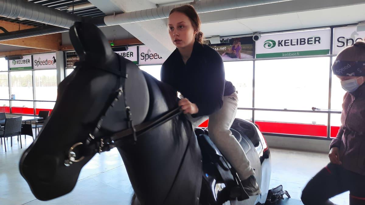 nainen ratsastaa simulaattorilla, valmentaja katsoo vierestä