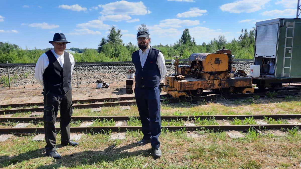 kaksi miestä junailijan puvussa