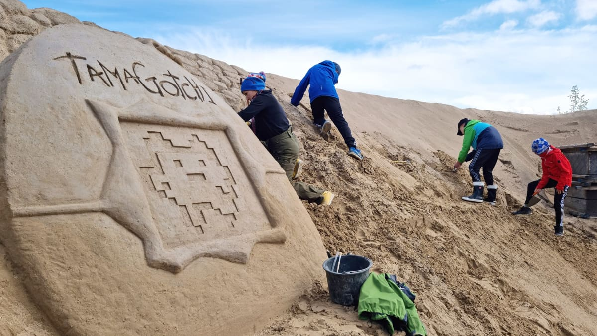 Ammattilainen ja oppilaita hiekkalinnaa rakentamassa