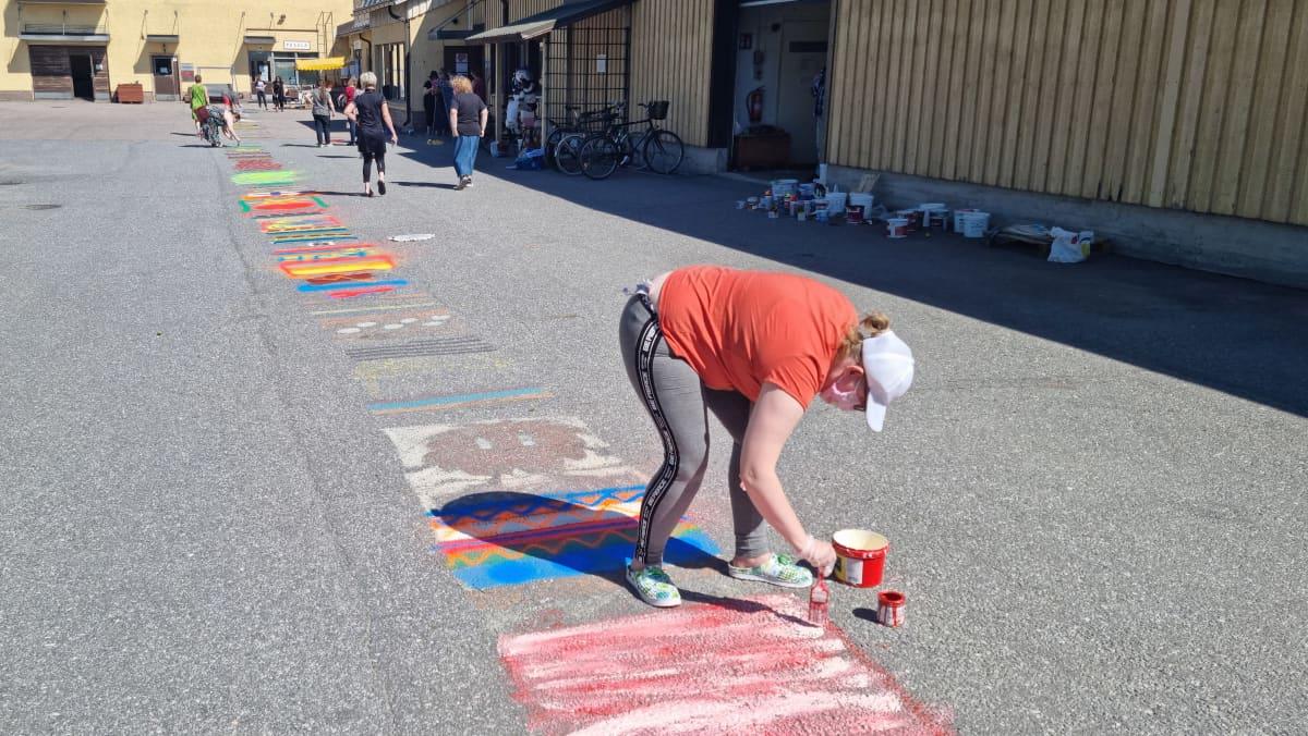 Laptuote säätiön pihan asfalttiin maalataan räsymattoa