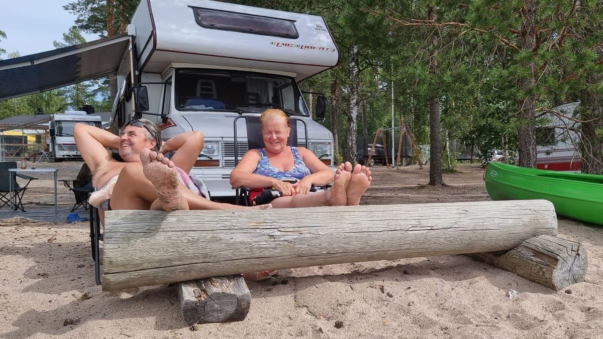 Juhani Hirvonen ja Virpi Hirvonen Liperistä ottavat aurinkoa Papiniemen uimarannalla