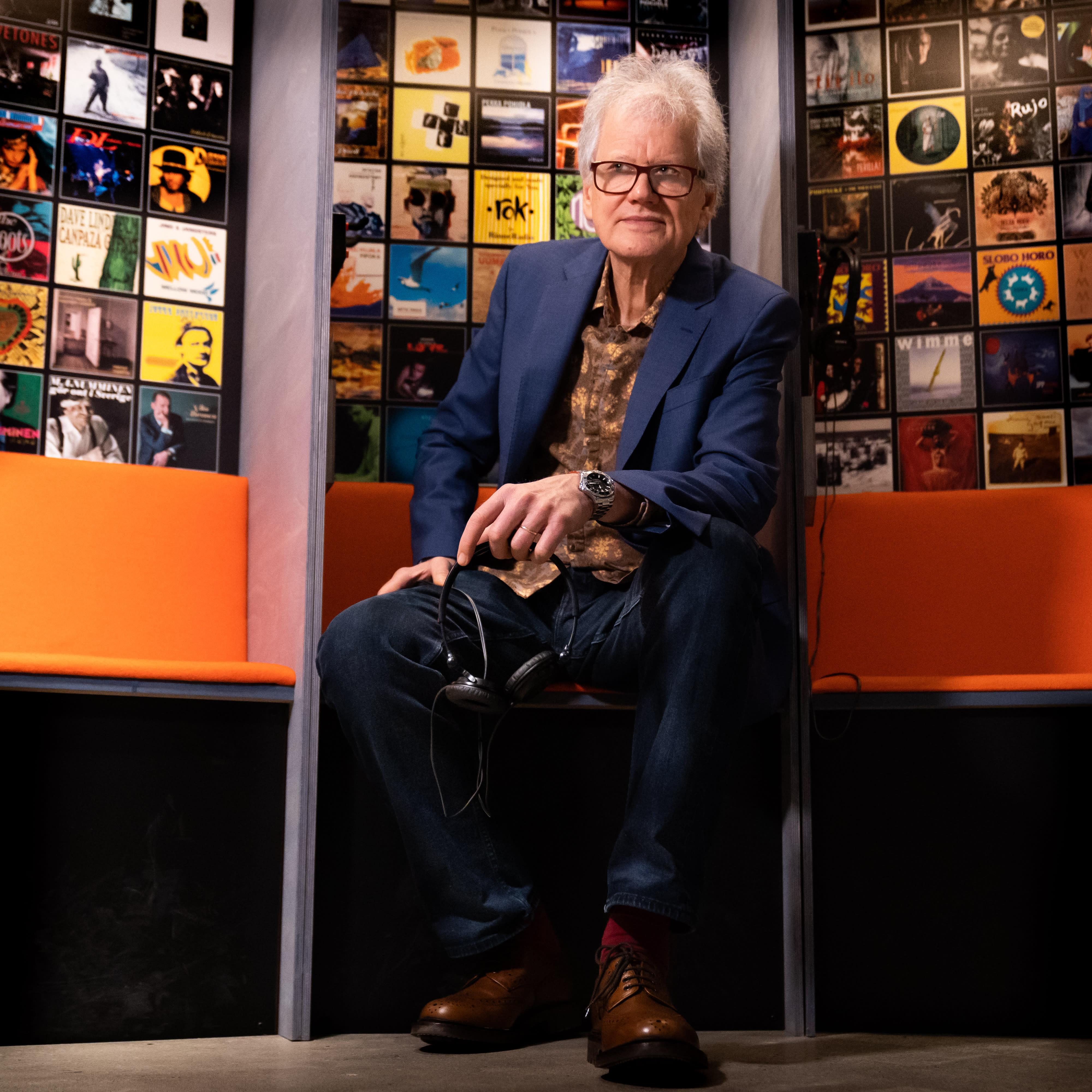 Tapio Korjus istuu penkillä Rockadillo - 50 vuotta kaikkiin suuntiin -näyttelyssä.