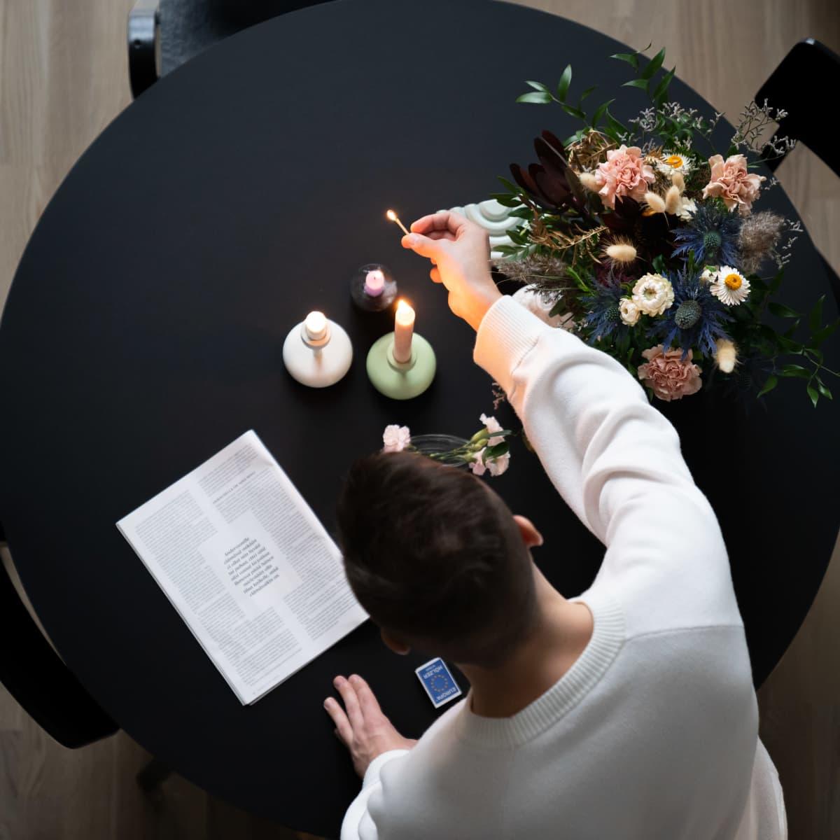 Joonas Pesonen sytyttää kynttilöitä keittiö pöydällä.