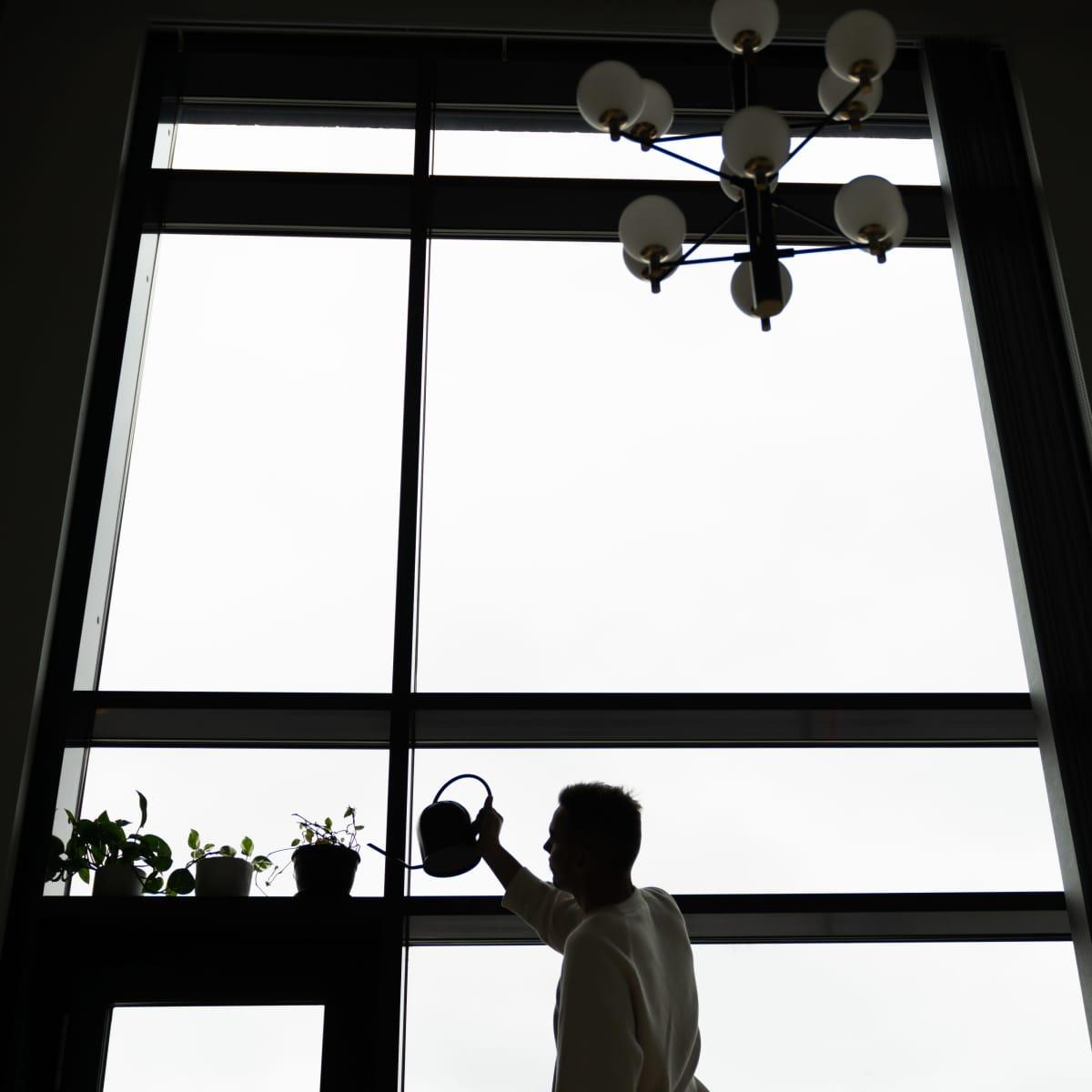 Joonas Pesonen kastelee kukkia ikkunalaudalla.