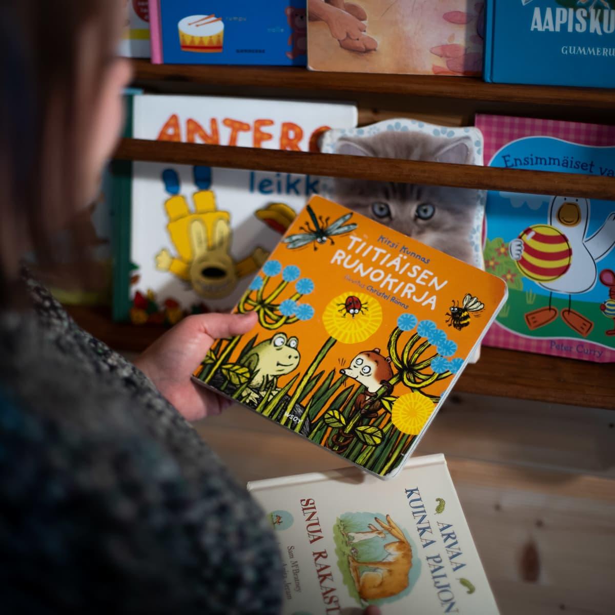 Nainen pitelee lastenkirjaa kädessään.