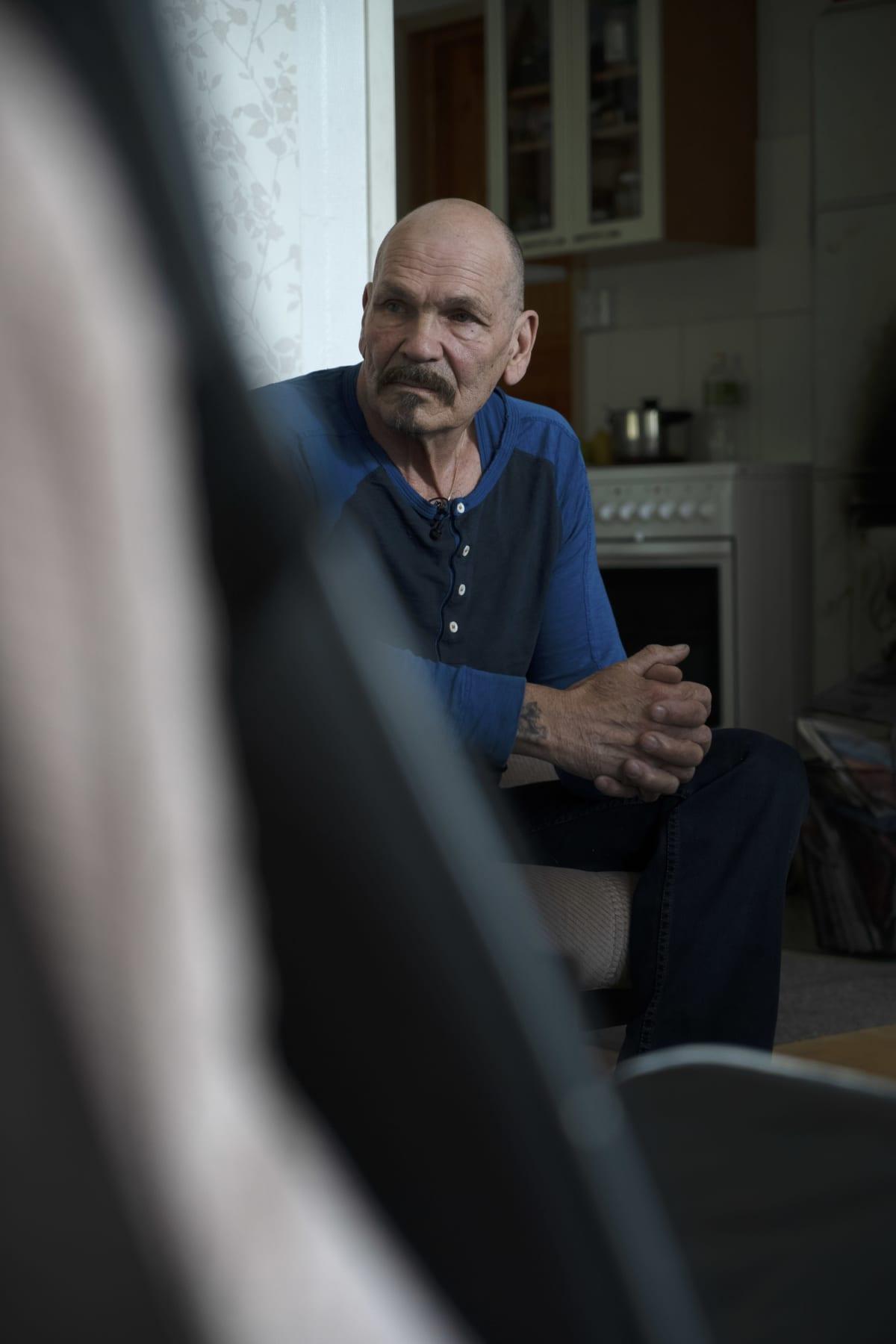 Arvi Savolaisen isä Paavo istuu sohvalla