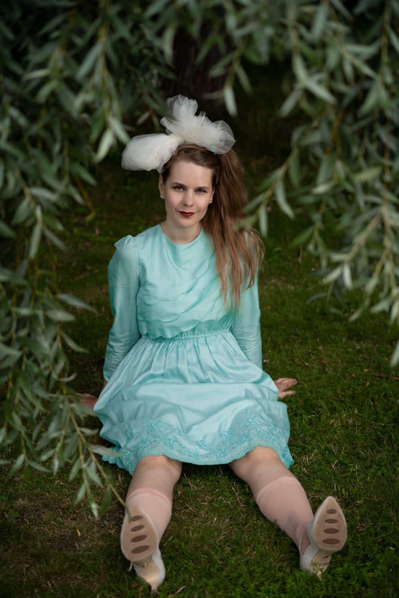 Ina Mikkola istuu nurmikolla.