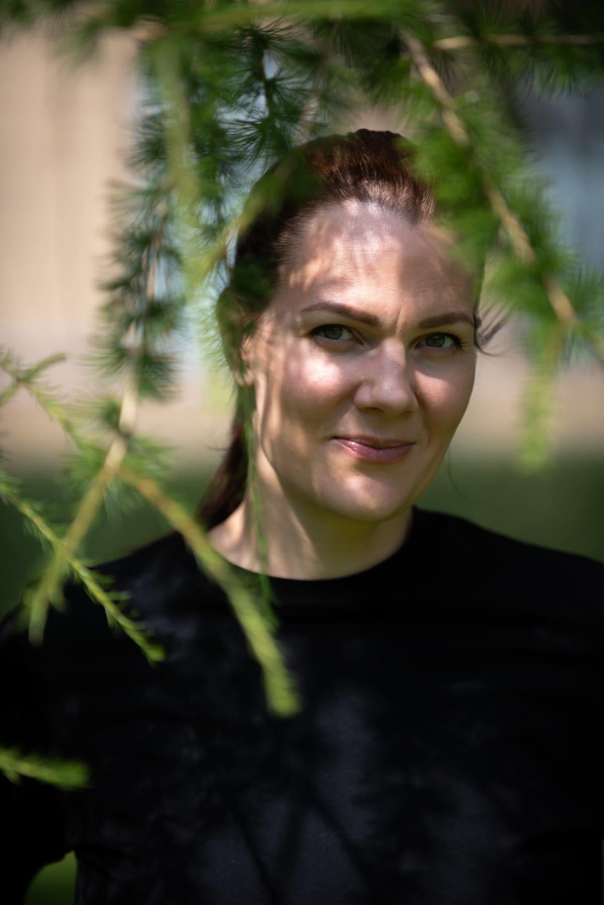 Outi Ellilä seisomassa puistossa, vihreät oksat kehystävät kasvoja.