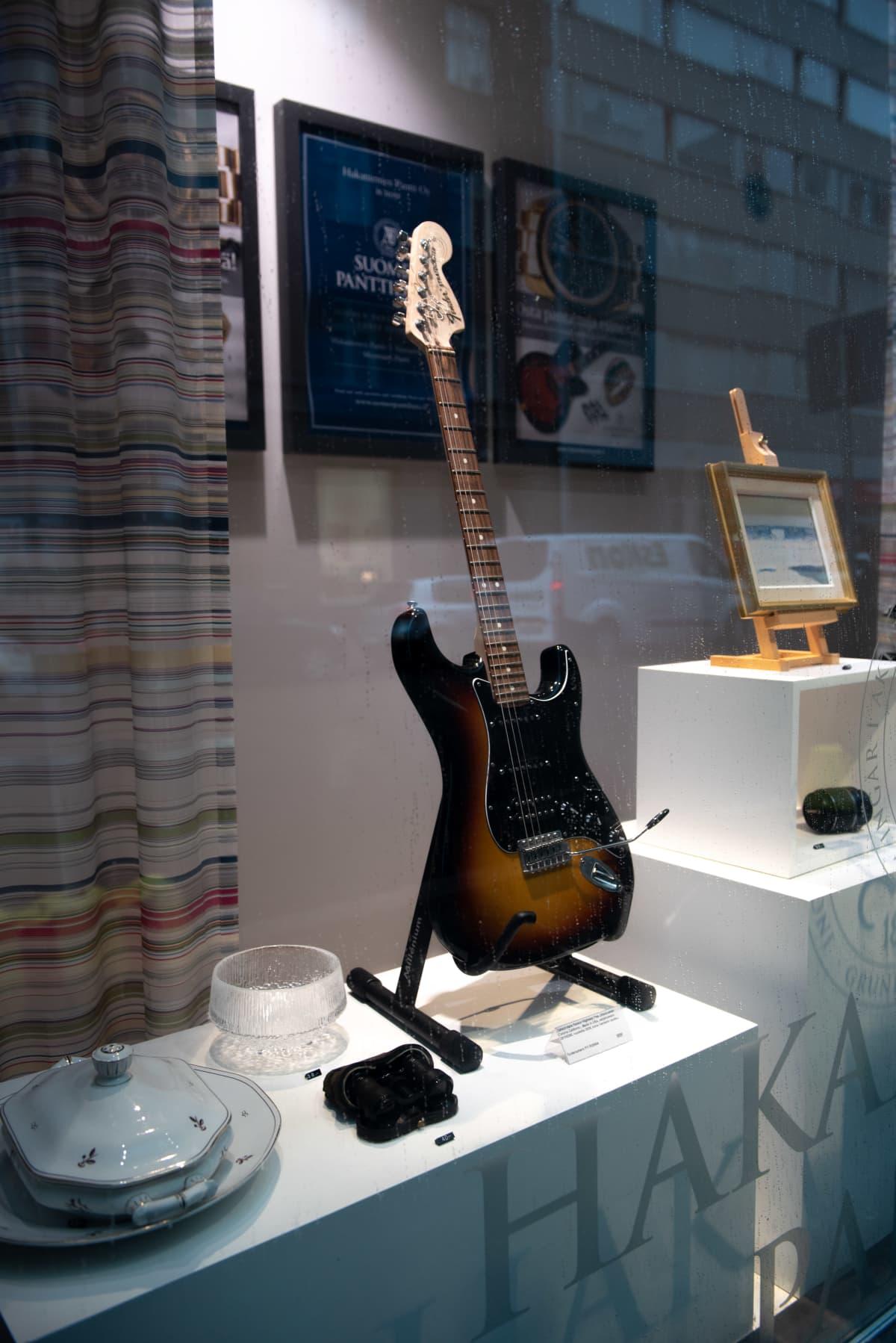 Näyteikkunassa kitara, kiikarit ja lasiesineitä.