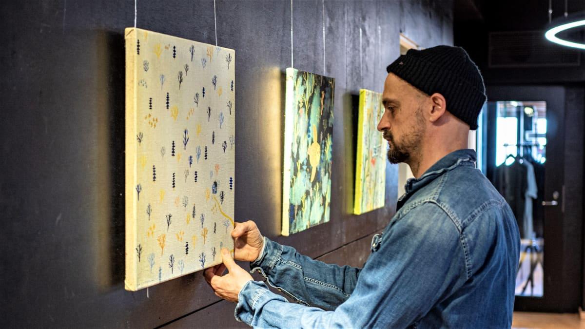 Kuvittaja Matti Pikkujämsä ripustaa taidenäyttelyä Limingan luontokeskuksssa.