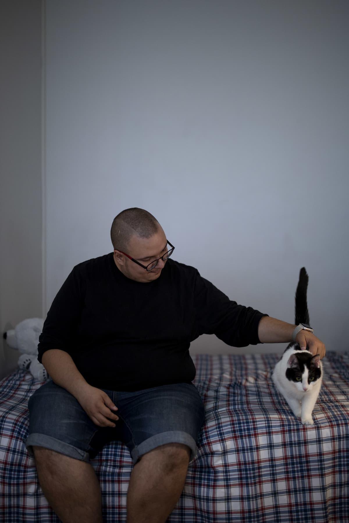 Benjamin Molini istumassa sängyllään kissansa kanssa.
