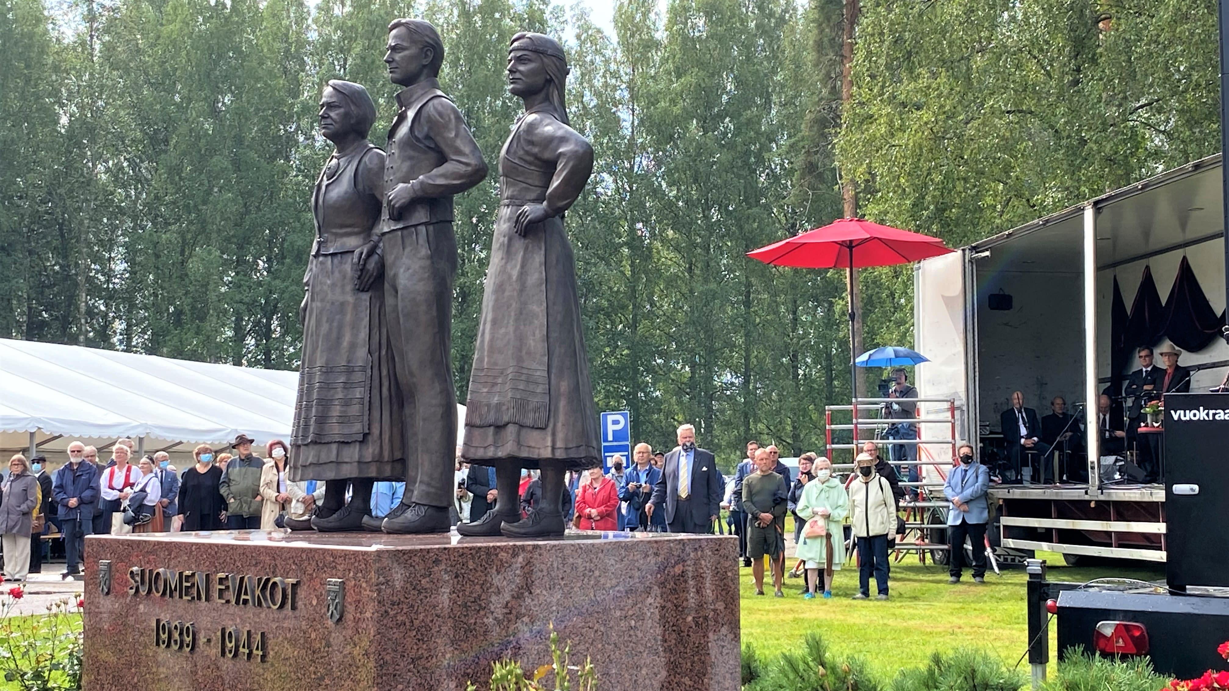Veistos jossa kolme ihmistä seisoo. Veistos puistossa, ihmisiä ympärillä.
