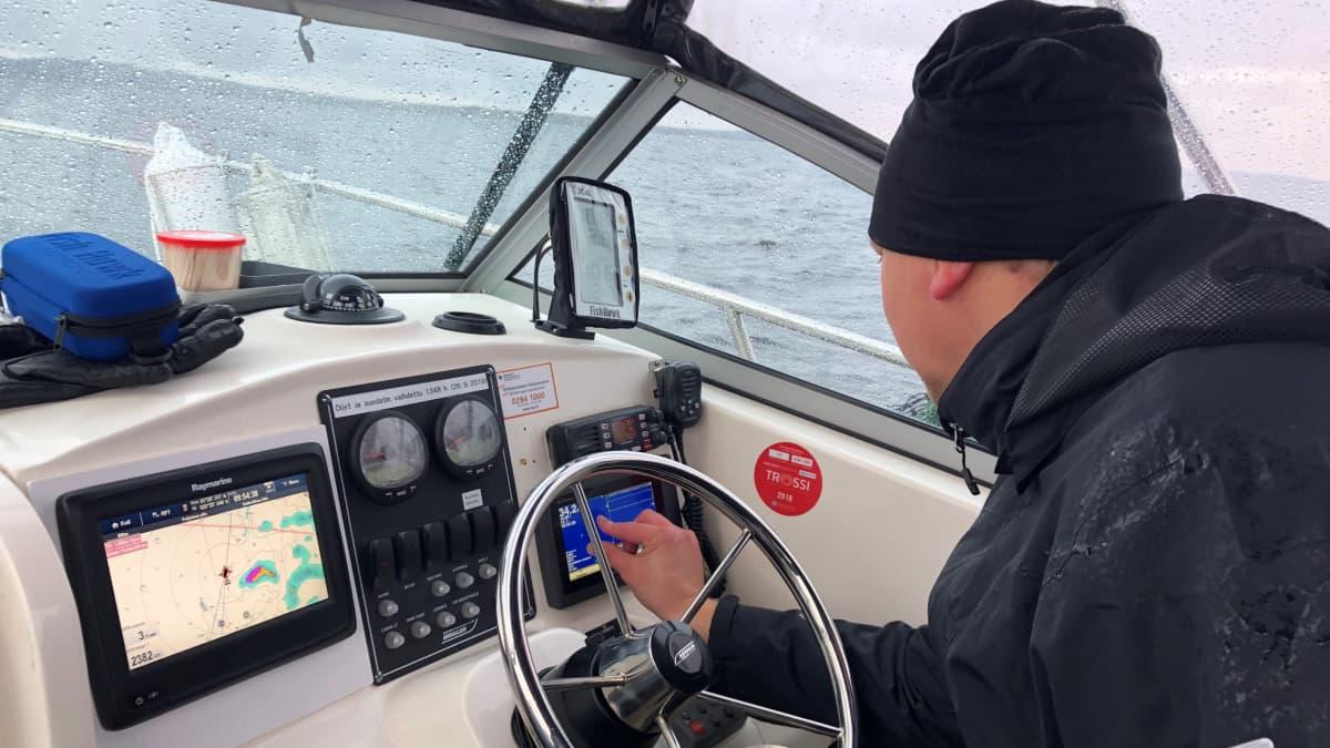 Veneen kuljettaja säätää karttaplotteria.