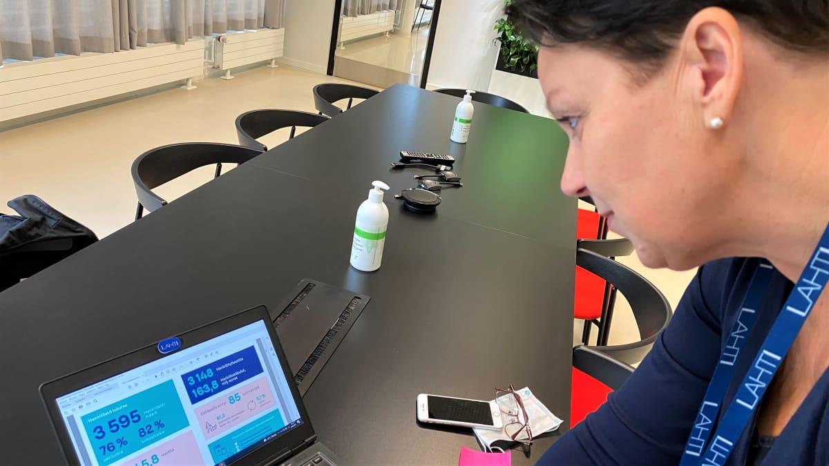 Nainen katsoo tietokoneen ruutua, ympärillään pöytä, tyhjiä tuoleja