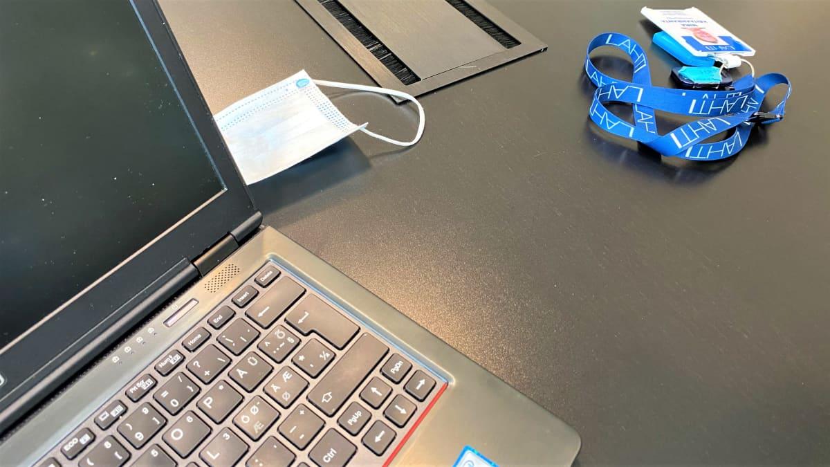 kannettavan tietokoneen ruutu, pöydällä kasvomaski, muovinen kulkukortti