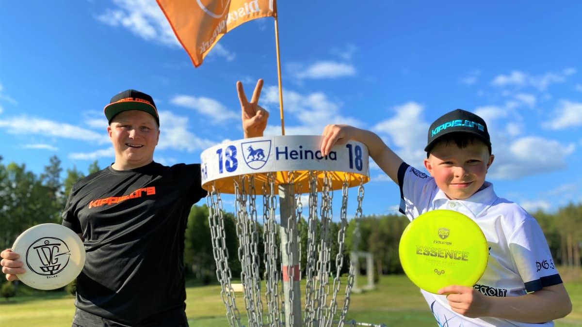 kaksi nuorta liitokiekot käsissään, nojaavat frisbeegolfkoriin