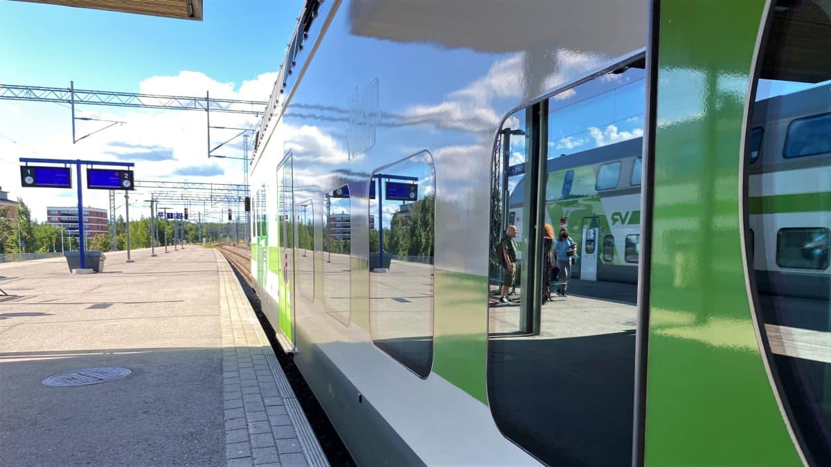Valkovihreä juna paikallaan vieressä harmaa ja tyhjä asemalaituri