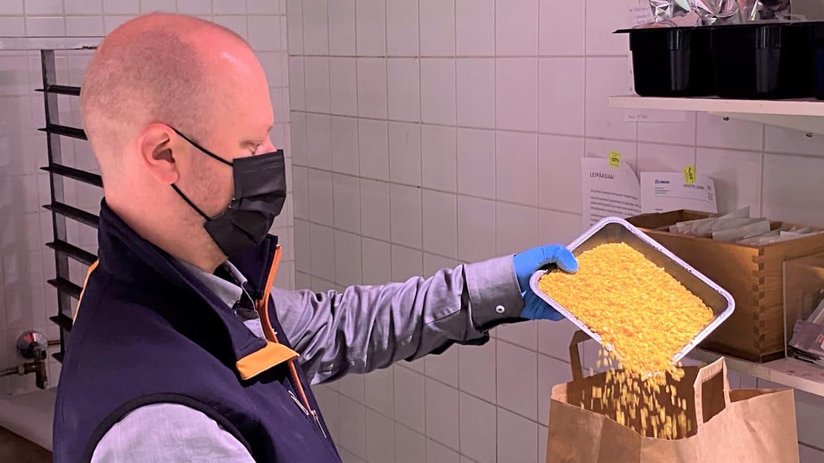 Mies kaatoo vehnäleipärouhetta paperipussiin