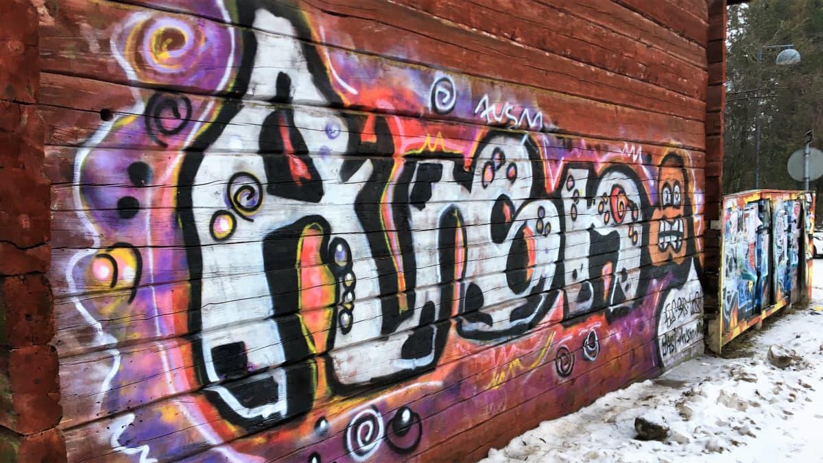 Graffitteja hirsitalon seinässä.