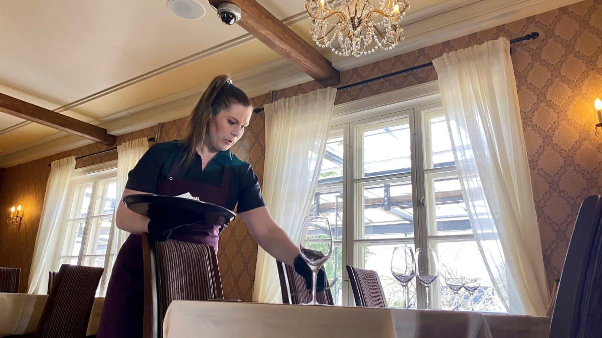 ravintolayrittäjä Anu Luukko kattaa pöytää