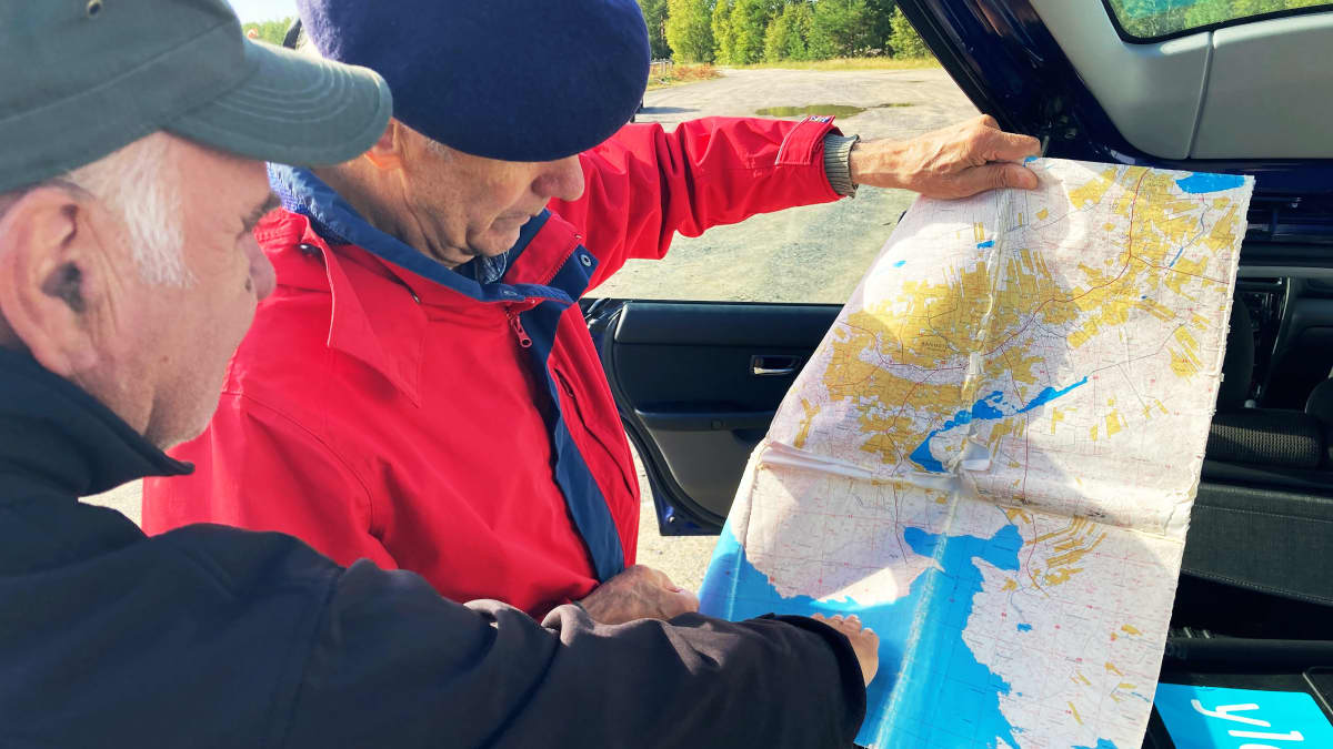 Markku Piekkola ja Pertti Rapinoja esittelevät isovihan aikasta murhapaikkaa kartalta Hailuodon kirkkosalmessa.