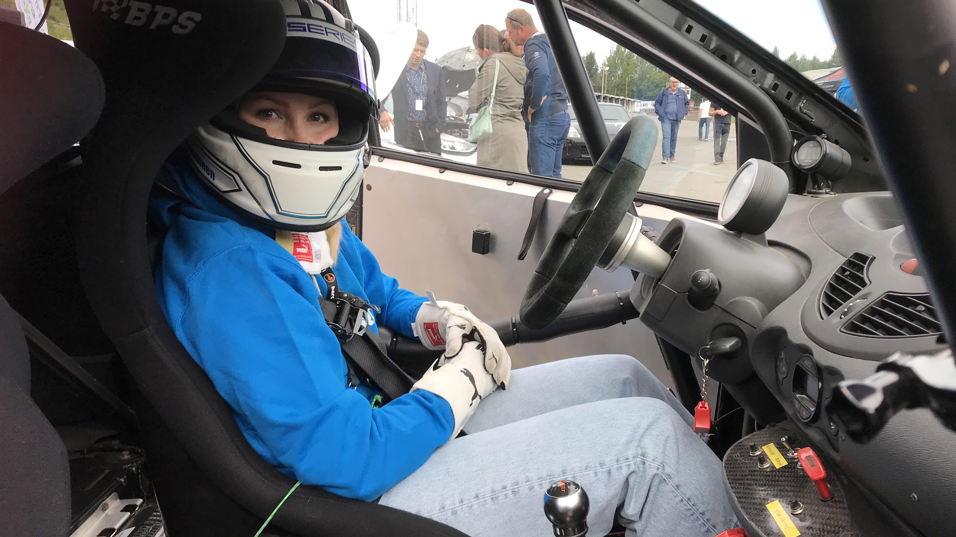 Kypäräpäinen nainen istuu kilpa-auton kuljettan paikalla
