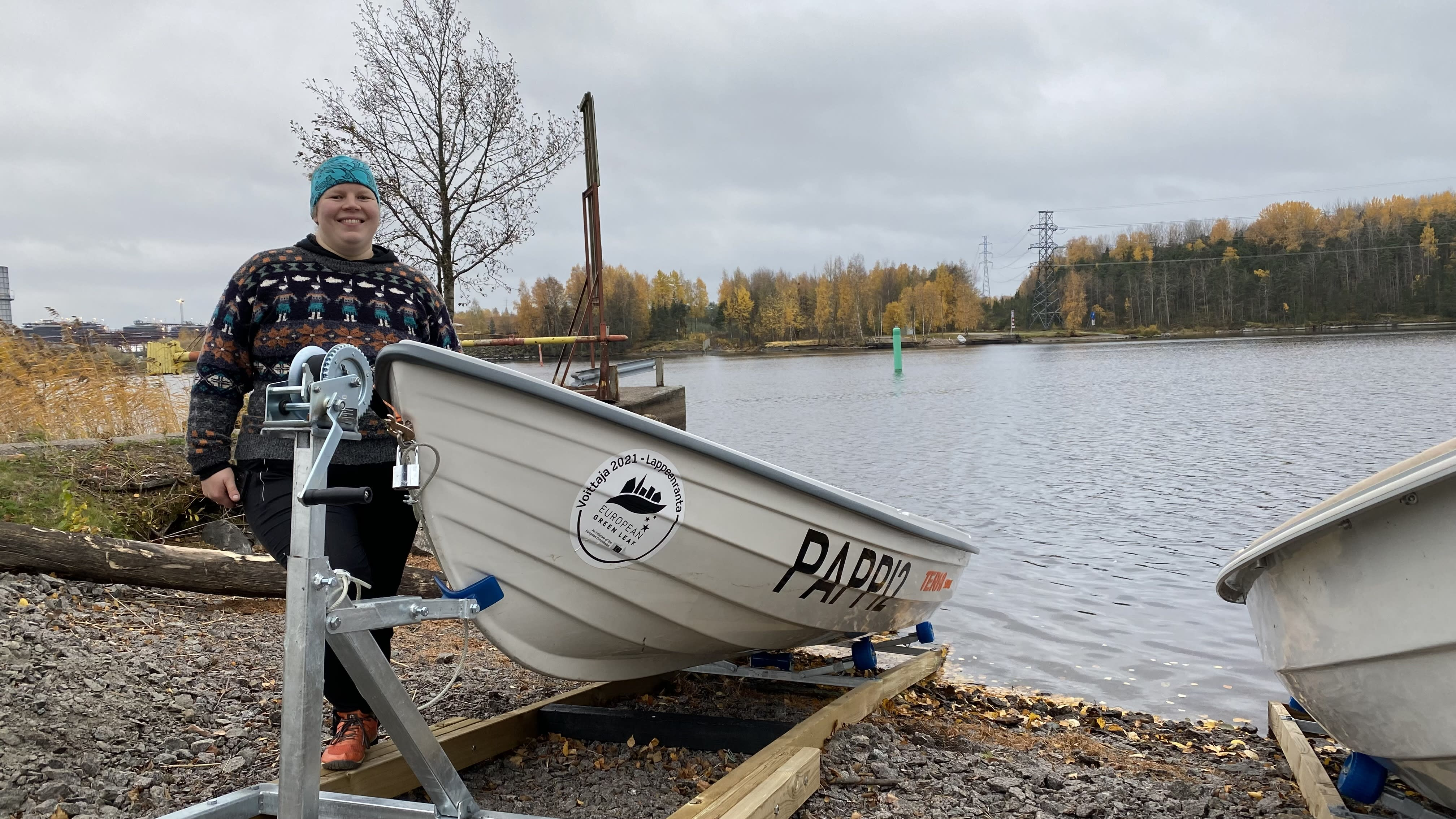 Reetta Valkonen rannassa soutuveneen vieressä