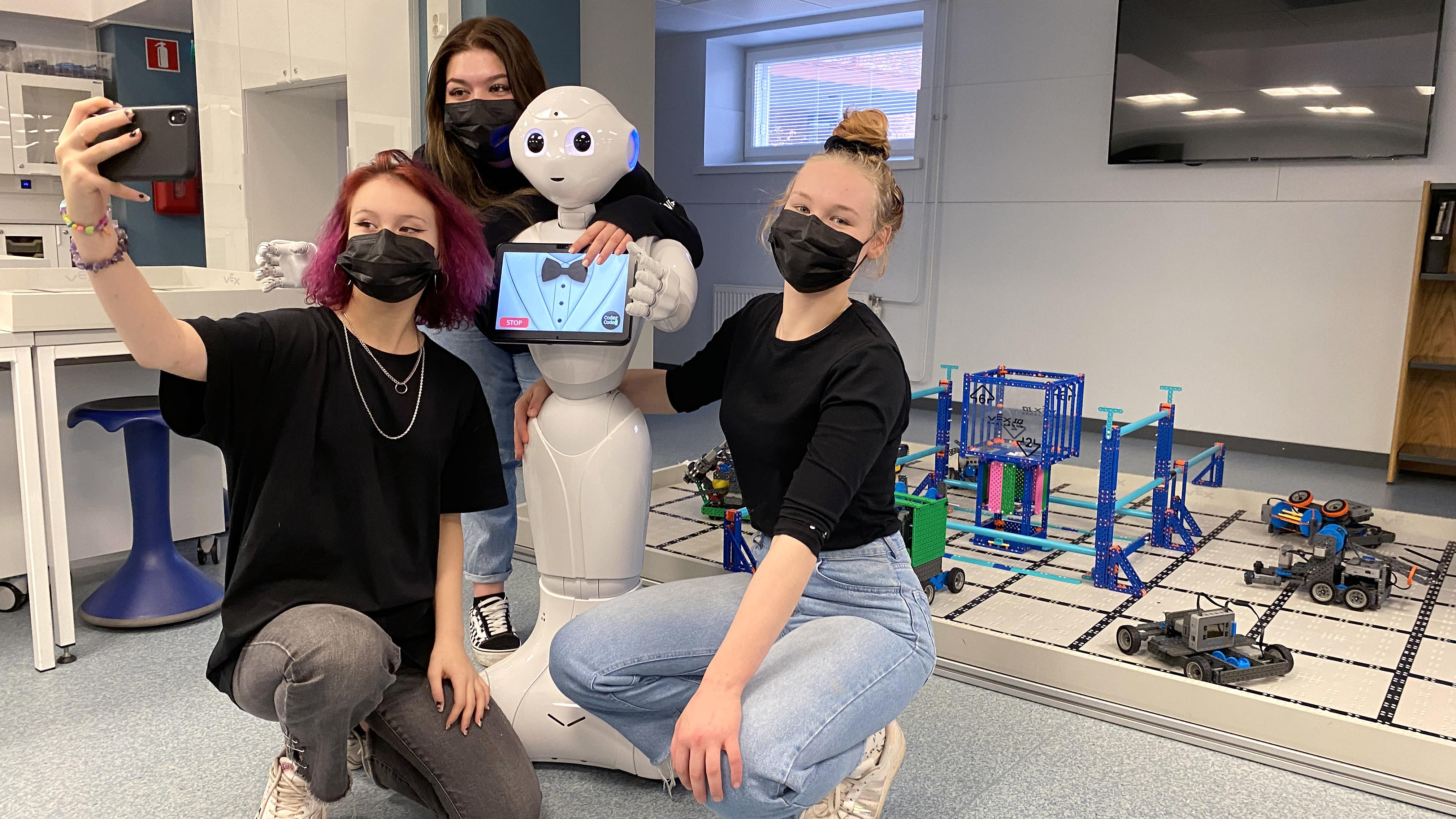 Jenna Hietakangas, Pinja Jokinen ja Sara Korkia-aho ottavat selfietä yhdessä ihmishahmoa muistuttavan humanoidirobotin kanssa.