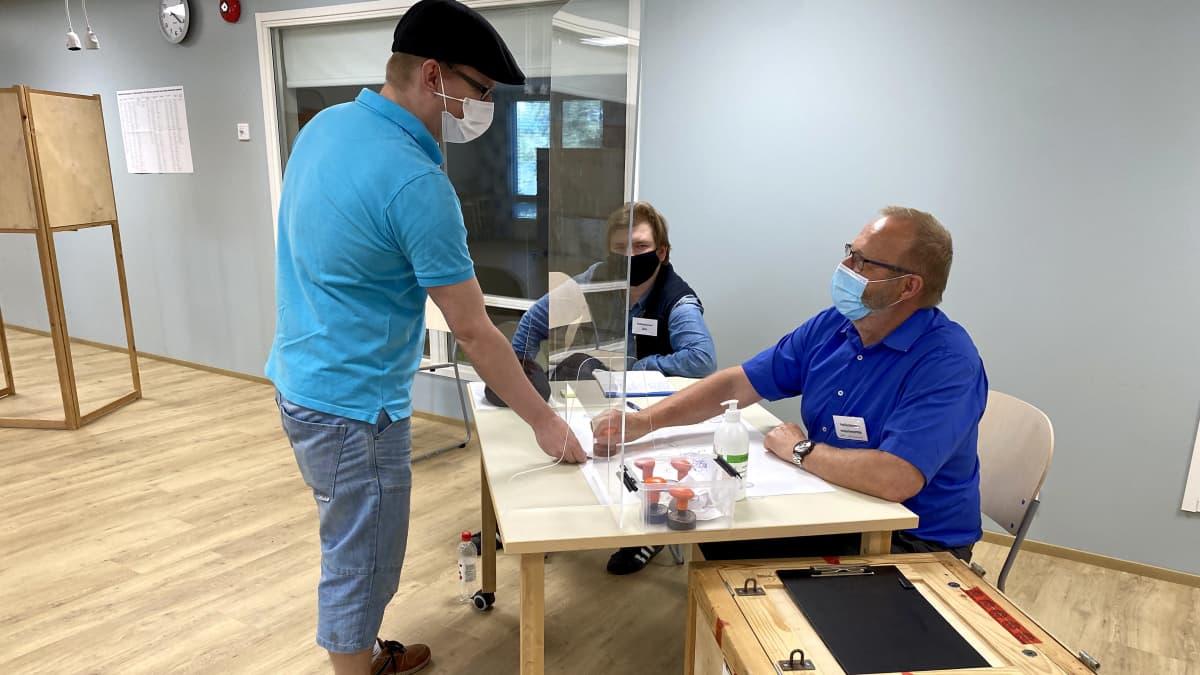 Mies äänestää kuntavaaleissa.