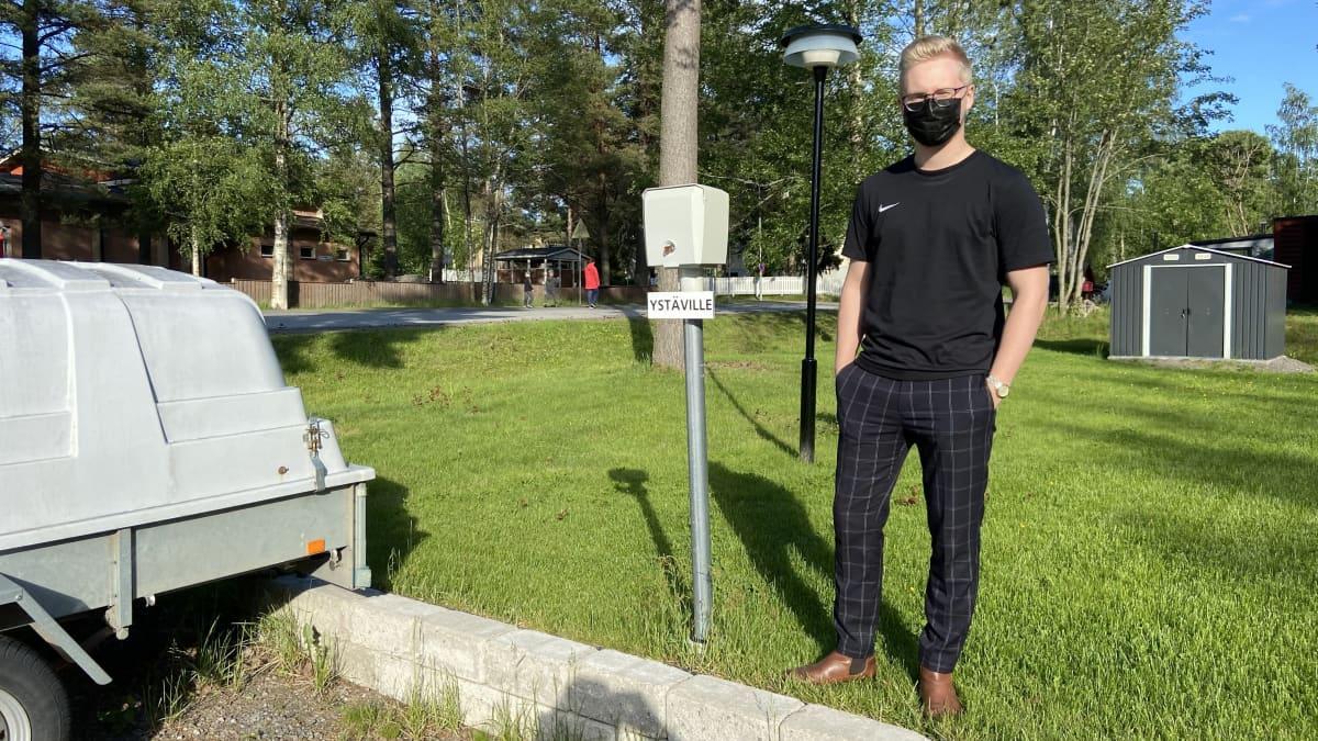 Kuvassa Nooa Kronqvist seisoo kotipihansa parkkipaikalla.